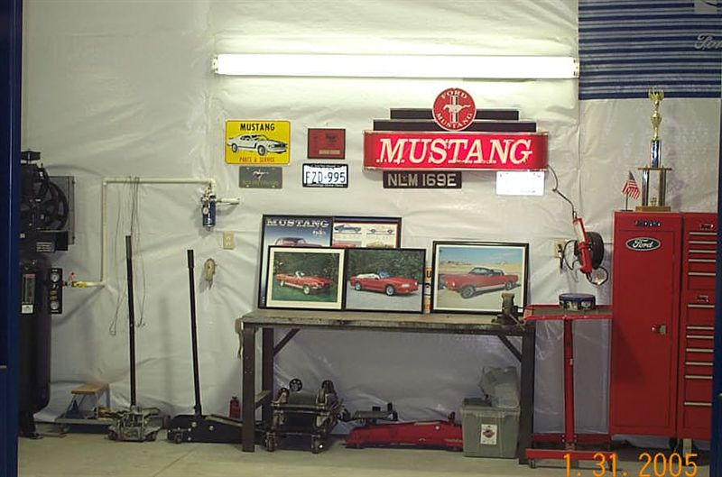 Neon Mustang sign, pictures of past cars and trophies.